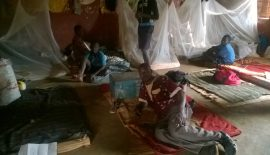 NEMACY-Uganda CEO lays down on papyrus mat in one of the improvised dormitory rooms at Mutai primary school.